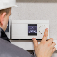 Technician adjusting thermostat for heating system